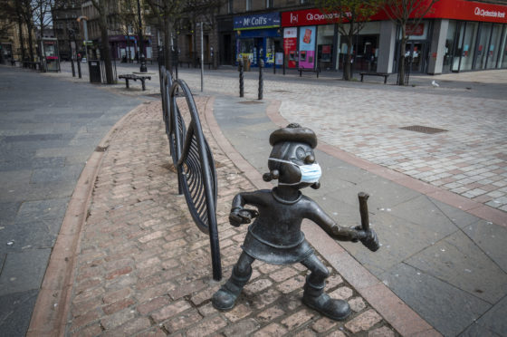 The statue of Beano character Minnie the Minx sports a protective face mask in Dundee city centre.