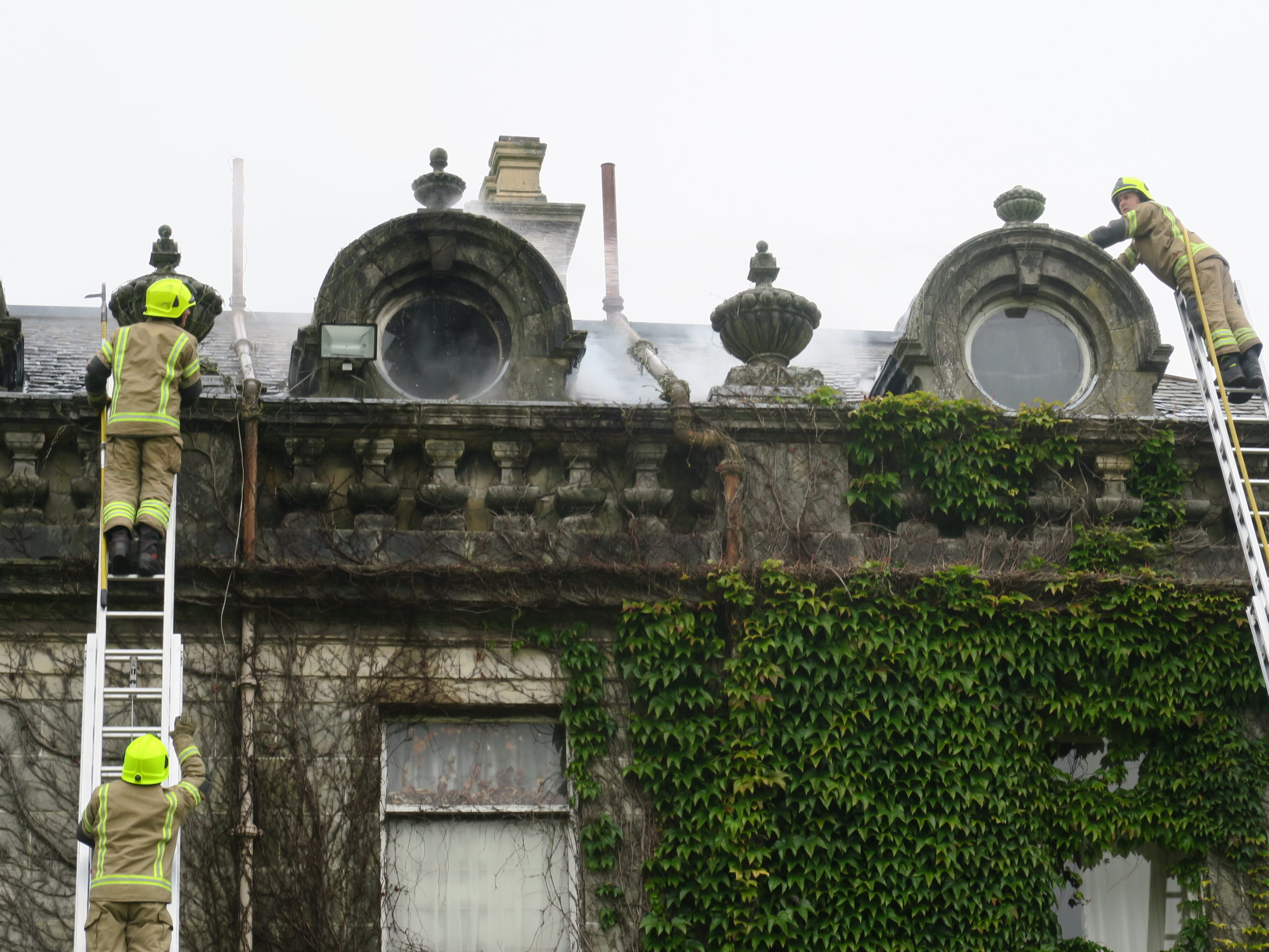 Firefighters on the roof of the main building at Letham Grange.