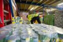Volunteers prepare pallets of food for distribution.