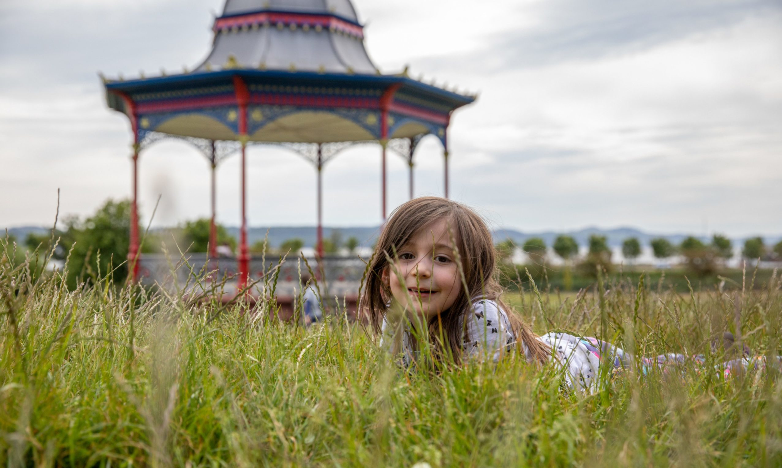 Zoe Maure exploring the long grass on the northern perimeter of Magdalen Green, Dundee.