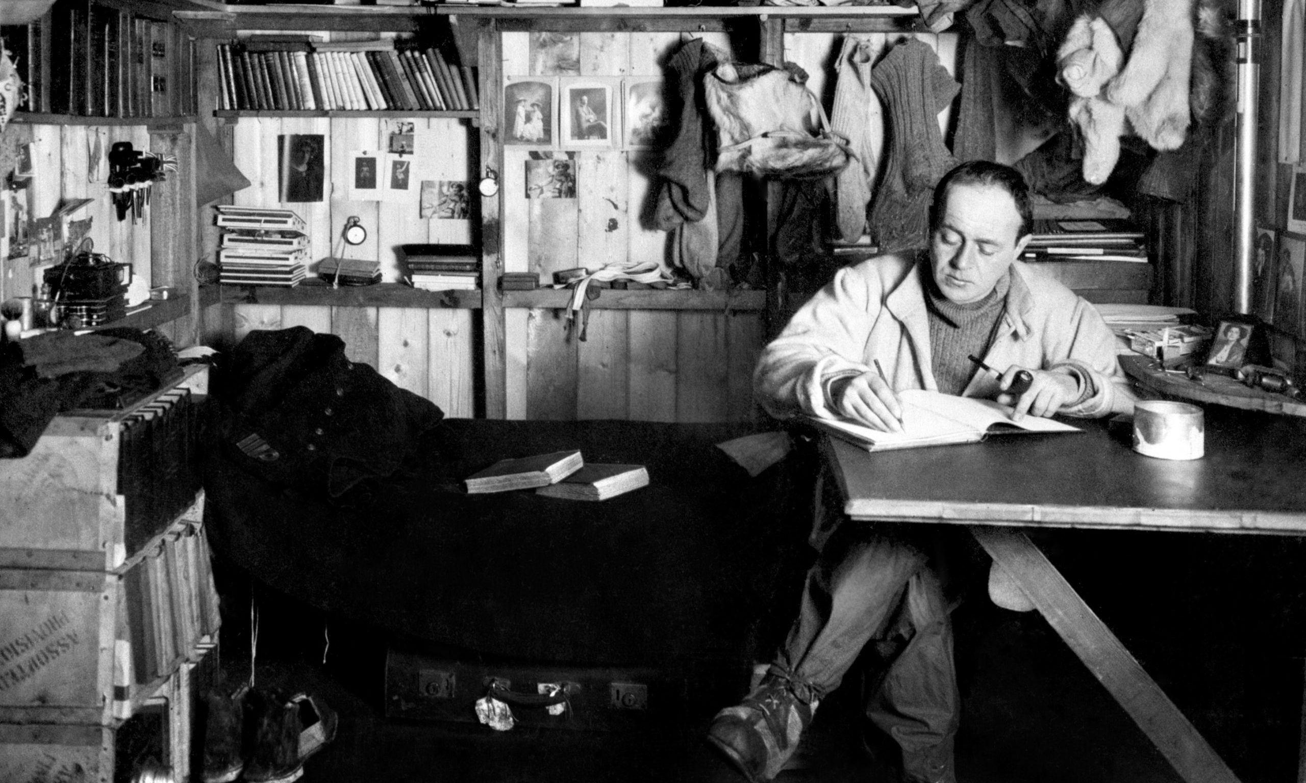 Captain Robert Falcon Scott writing at a table in his quarters (known as his 'den') at the British base camp in Antarctica.