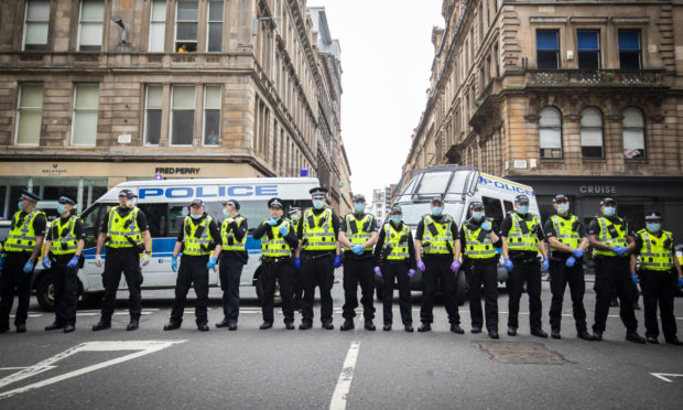 Police hold back protesters at a demonstration organised by the Loyalist Defence League in George Square in Glasgow.