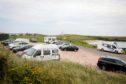 Campervans and cars filling up the car park and roadside as tourists arrive in Campervans to enjoy Fife.