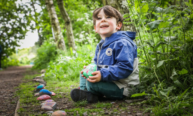 The Courier, CR0021700, News, Emma Crichton story, Harry Boa, the lockdown snake made of painted stones at Forfar Loch. Picture shows; Isaac Herd, 4, with the snake. Friday 5th June, 2020. Mhairi Edwards/DCT Media