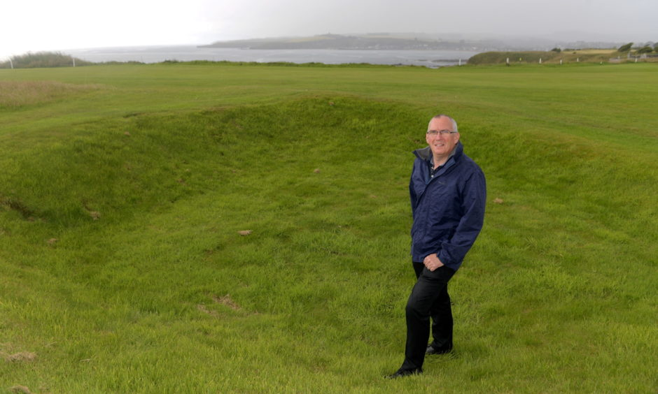 Club manager Stewart Kerr standing in Hitler's Bunker, the remnants of a crater left by a World War Two bomb between the first and second fairways of the course.