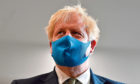Prime Minister Boris Johnson, wearing a face mask during a visit to the headquarters of the London Ambulance Service NHS Trust.