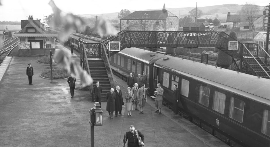The Queen and Duke of Edinburgh exit a train at Alyth Station in October 1957.