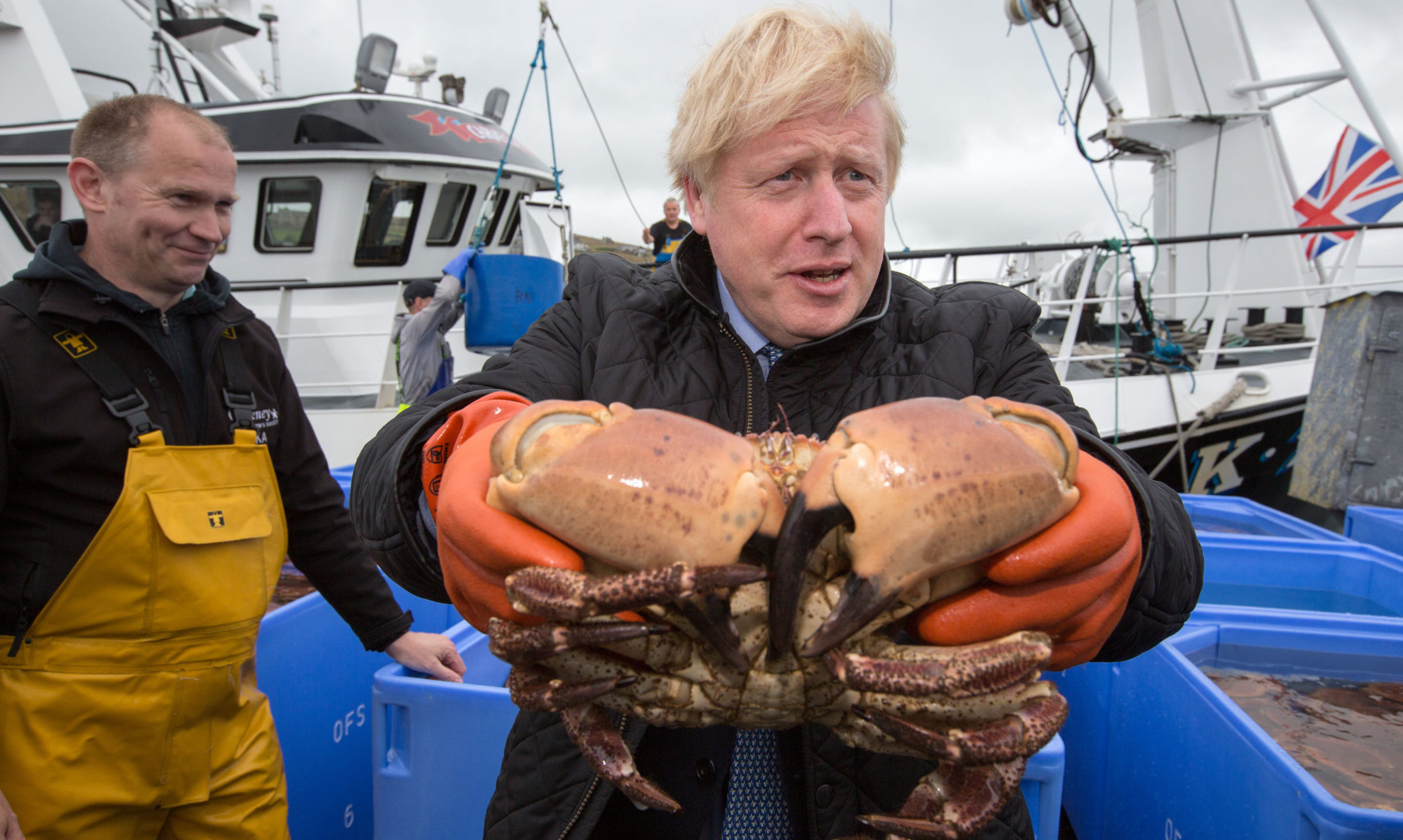 Prime Minister Boris Johnson holds crabs caught on the Carvela with Karl Adamson at Stromness Harbour during a visit to Scotland.