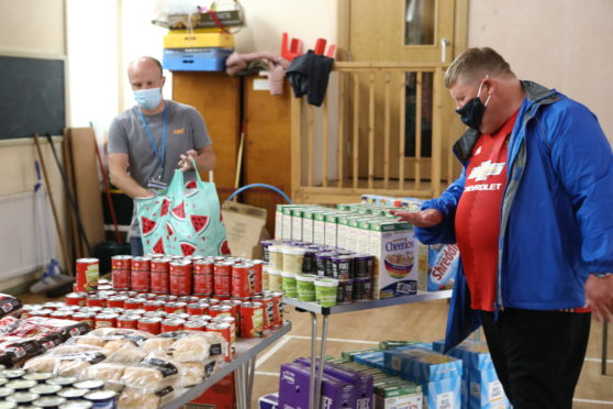 Ross Clark - Community Volunteer serving Christopher McIntosh, at the Fintry Food Larder, in Fintry Parish Church, Dundee.