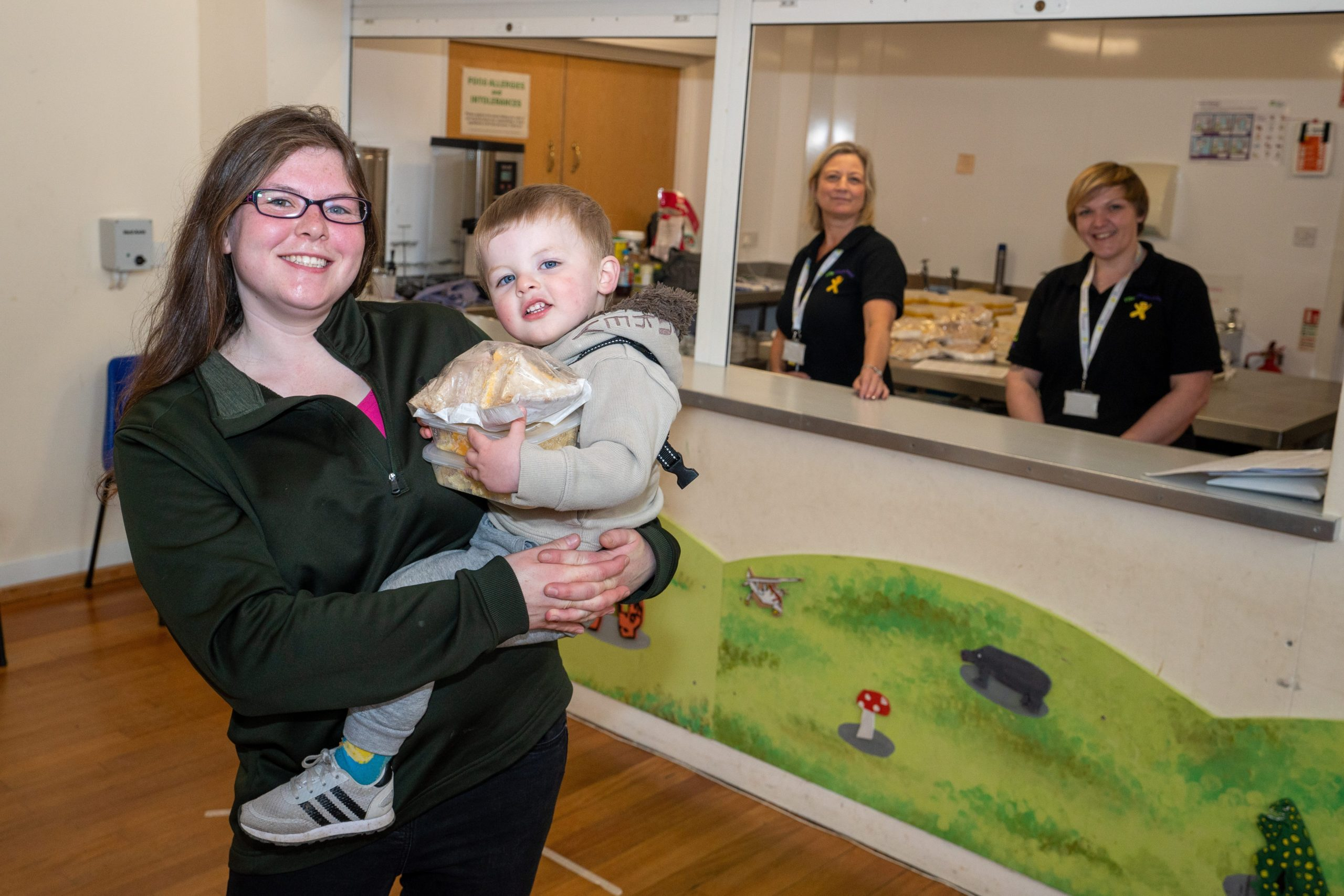 Jillian Cartmel, who is accompanied by her one-year-old son Lucas, collecting lunch from Zoe Taylor and Kerry Jones.