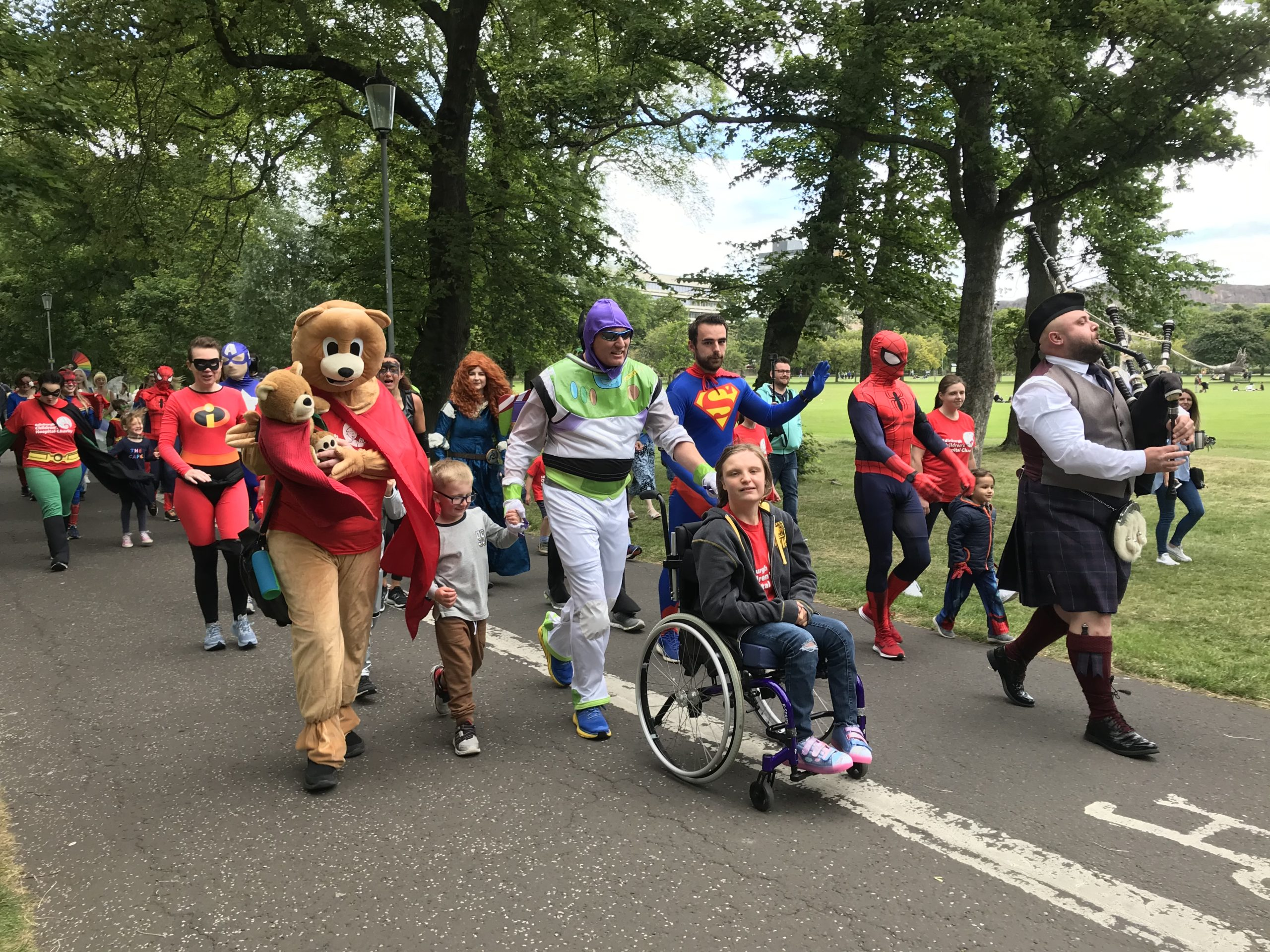 The Fife superheroes are piped in through the Meadows before arriving at the Sick Kids Hospital.