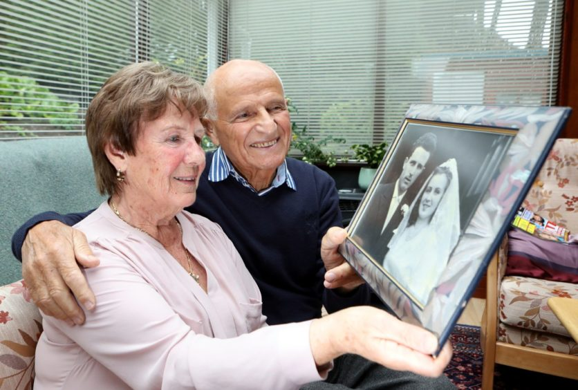 Betty and Peppino Lapadula look at a picture of their 1960 wedding, which took place at St Marys Lochee church.
