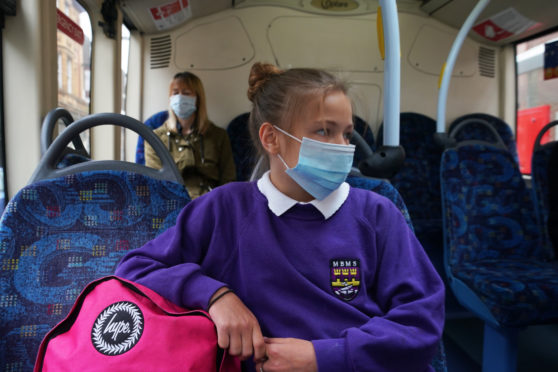 A school pupil wearing a face mask on a bus in Newcastle as face coverings become mandatory on public transport in England with the easing of further lockdown restrictions during the coronavirus pandemic. PA Photo. Picture date: Monday June 15, 2020. See PA story HEALTH Coronavirus FaceCoverings. Photo credit should read: Owen Humphreys/PA Wire