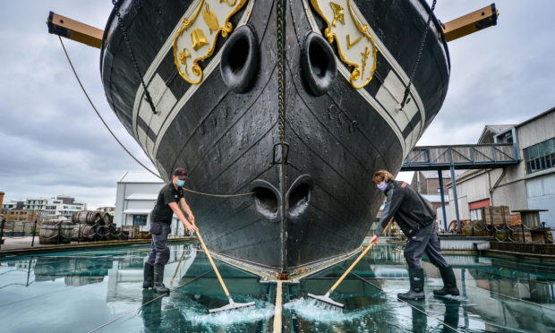 Technical services staff clean the surface of the glass sea, which is a series of glass plates surrounding Brunell's SS Great Britain and filled with water to create a sea effect, as the attraction reopens on Saturday, July 18, marking the 50th anniversary of the ship's return back home to Bristol, after the lifting of further coronavirus lockdown restrictions in England. PA Photo. Picture date: Thursday July 16, 2020. See PA story HEALTH Coronavirus. Photo credit should read: Ben Birchall/PA Wire