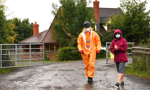 Karen Wright (left), Director of Public Health for Herefordshire CCG, sanitising before opening a gate to give a press statement outside Rook Row Farm in Mathon, near Malvern, Herefordshire, where there have been more than 90 positive cases of coronavirus confirmed.