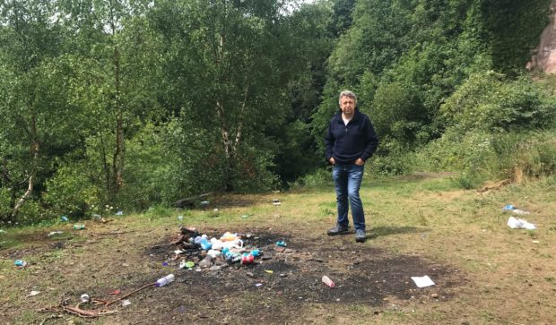Councillor Angus Forbes next to some of the discarded rubbish at Kingoodie.