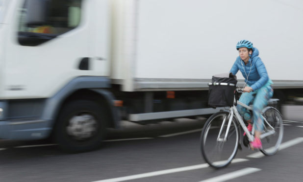 A cyclist and a lorry travel across a roundabout in Westminster, London.