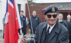 Captain Davidson raises the Red Ensign at a ceremony in Arbroath in 2018.