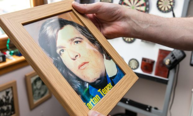 Wullie Burness holds a framed picture of his friend Jocky Wilson.