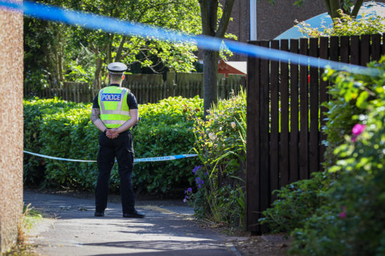 An officer guards the property in Meldrum Gardens, Glenrothes where the 83-year-old was attacked.