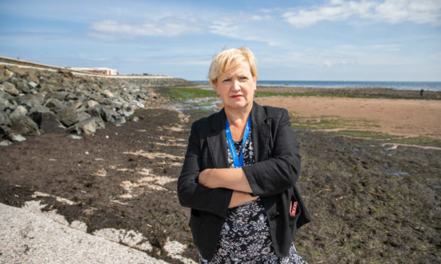Councillor Brenda Durno in front of the seaweed at West Links beach.