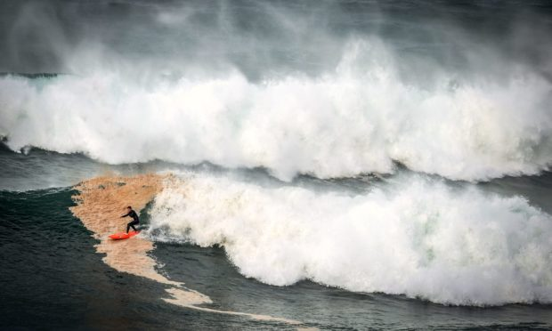 A surfer rides a large wave at Warriewood Beach during a stormy day.