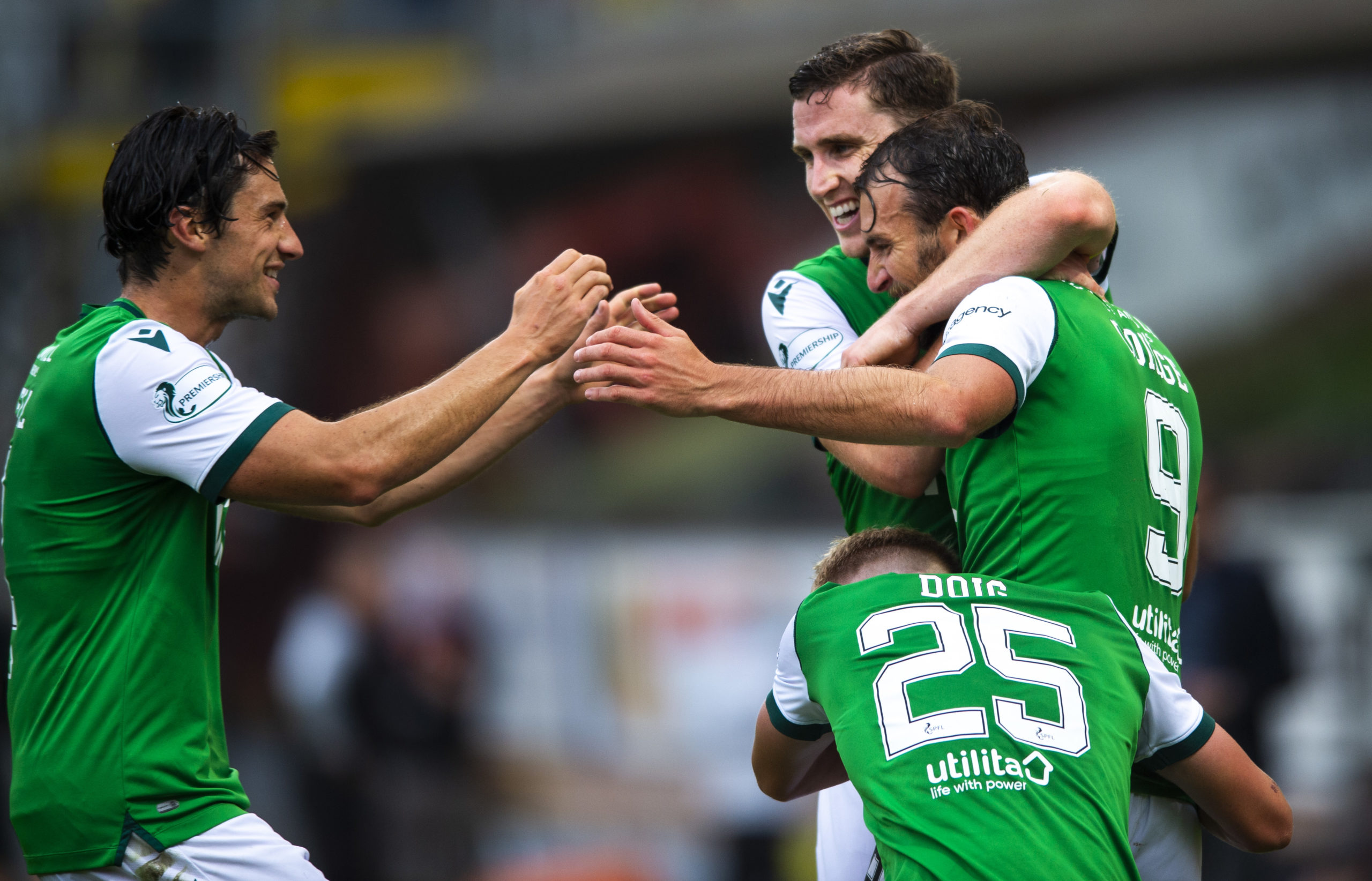 Christian Doidge (No 9) is mobbed after netting the winner for the Hibees.