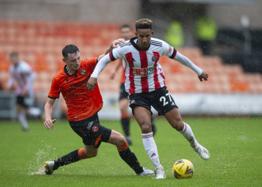 United kid Kerr Smith challenges Sheffield United star Callum Robinson in wet conditions.