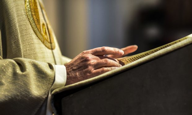 The hands of a catholic priest reading a bible.