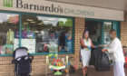 Barnardo's Dalgety Bay manager Theresa Allan accepts a donation from a customer.