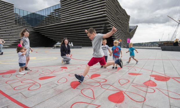 Jack Coulthard, 8, plays on the new interactive playground with Kirsty Hassard, curator at V&A Dundee.