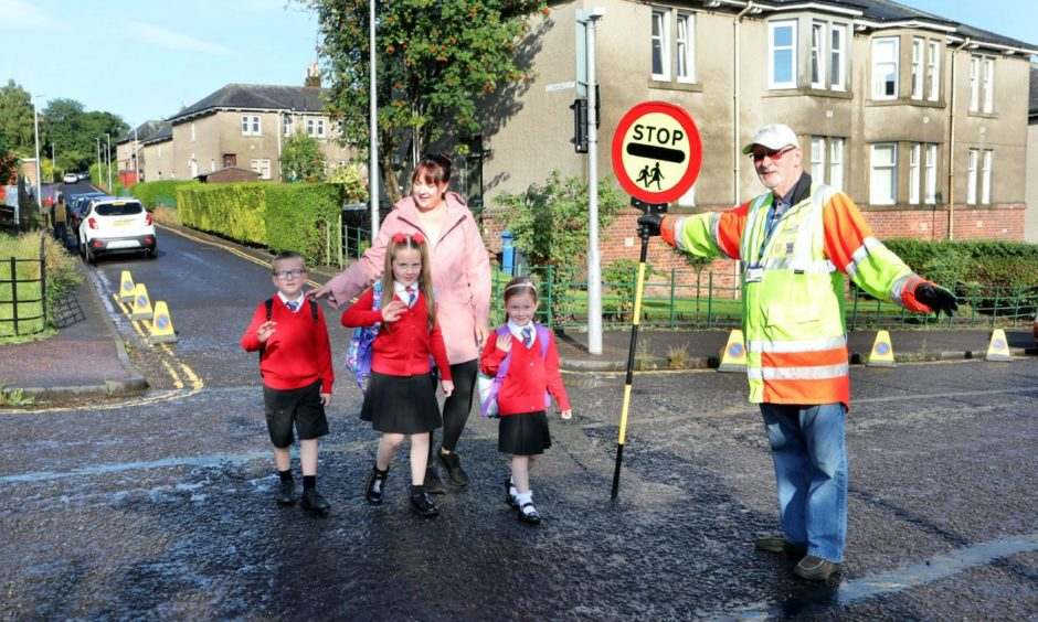 Victoria Park pupils Tabitha Banner, Robin Banner with their mum Kelly and Lily McLuskey cross the road with lollipopman Derick Thompson