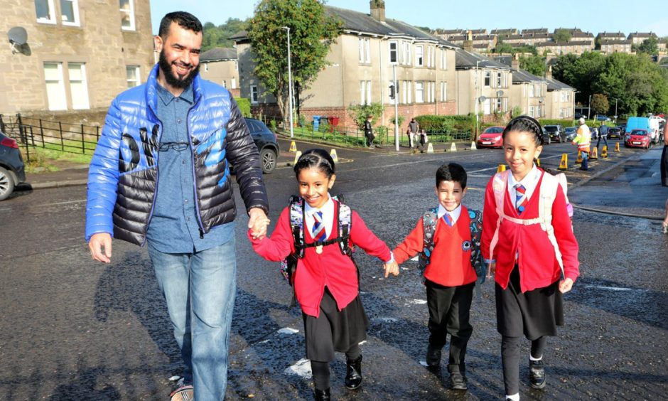 A father walks his kids to school this morning