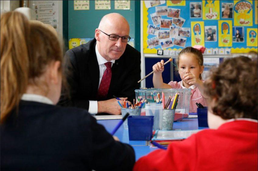 Education Secretary John Swinney helps youngsters learn before the coronavirus pandemic closed schools.
