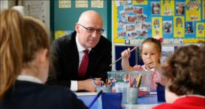 Education Secretary John Swinney helps youngsters learn before the coronavirus pandemic closed schools.