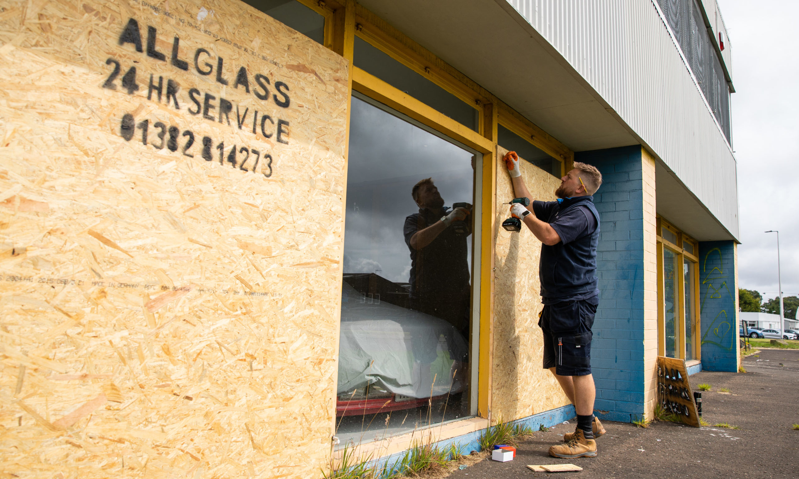Workers repair the broken windows at the Carmeleon Preparation Centre.