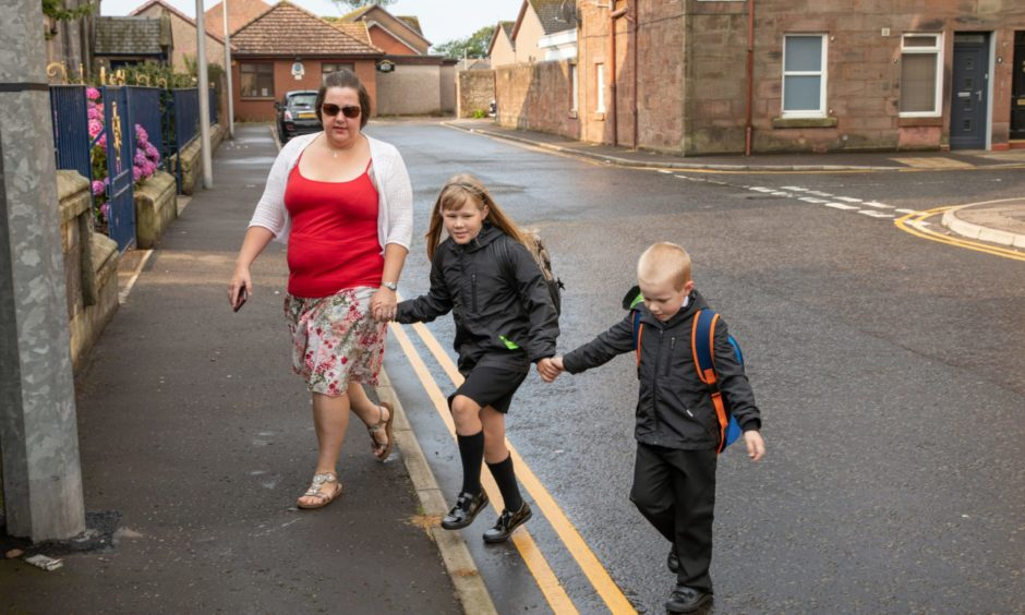 Dawn Dundas helps her children, Kaylee (9) and Calvin (5) getting ready to go back to Ladyloan Primary School,