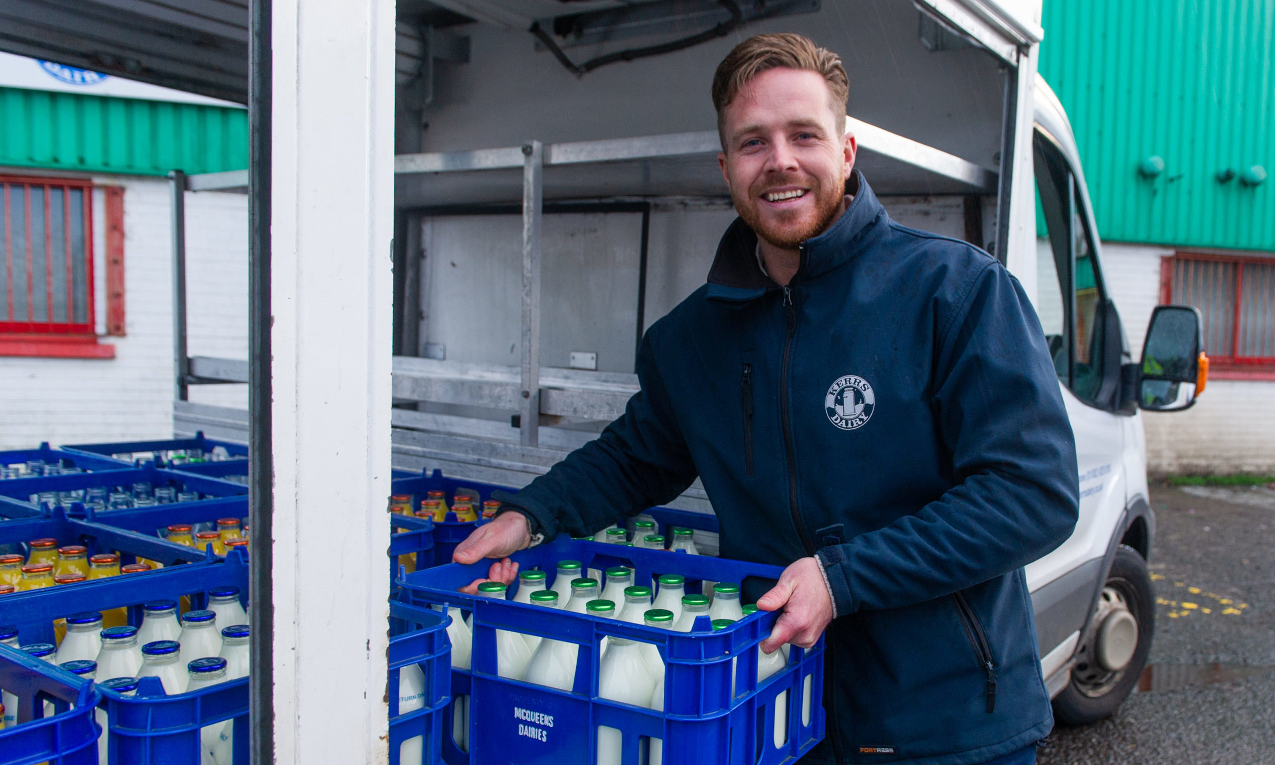 Kelvin Kerr Jnr with a crate of glass milk bottles.