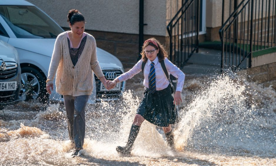 Lee Dennis and her daughter Heidi (12) fight their way through the flood water on Windsor Terrace.
