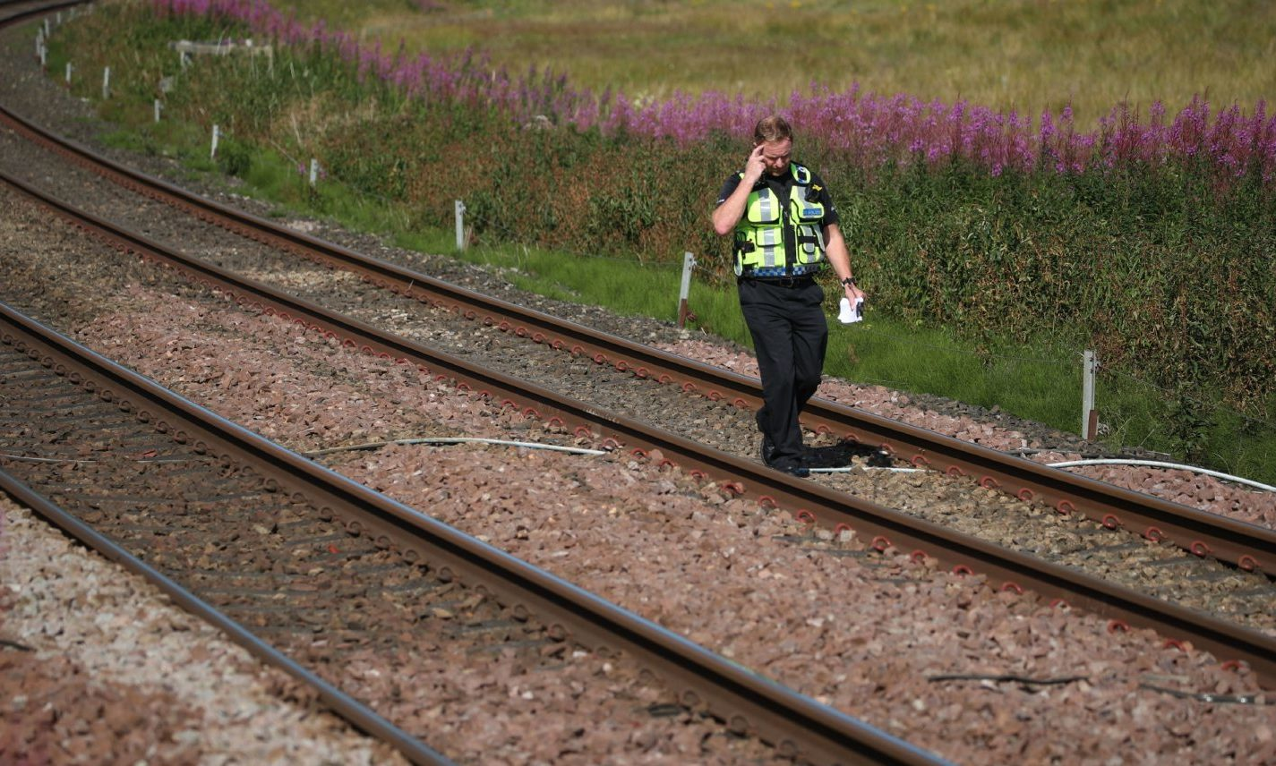A police officer walks along the tracks at Carmont crossing on the train of the tragedy.