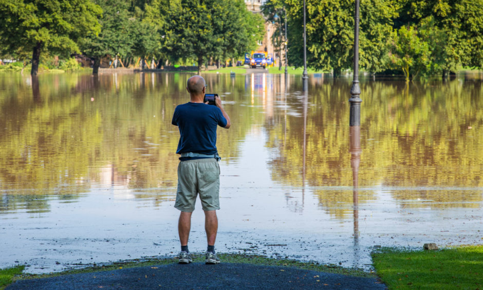 A man looks out at the flooding on the South Inch.