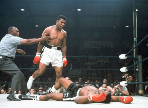 Muhammad Ali is held back by referee Joe Walcott, left, after Ali knocked out Sonny Liston in the first round of their 1965 title fight in Lewiston, Maine.