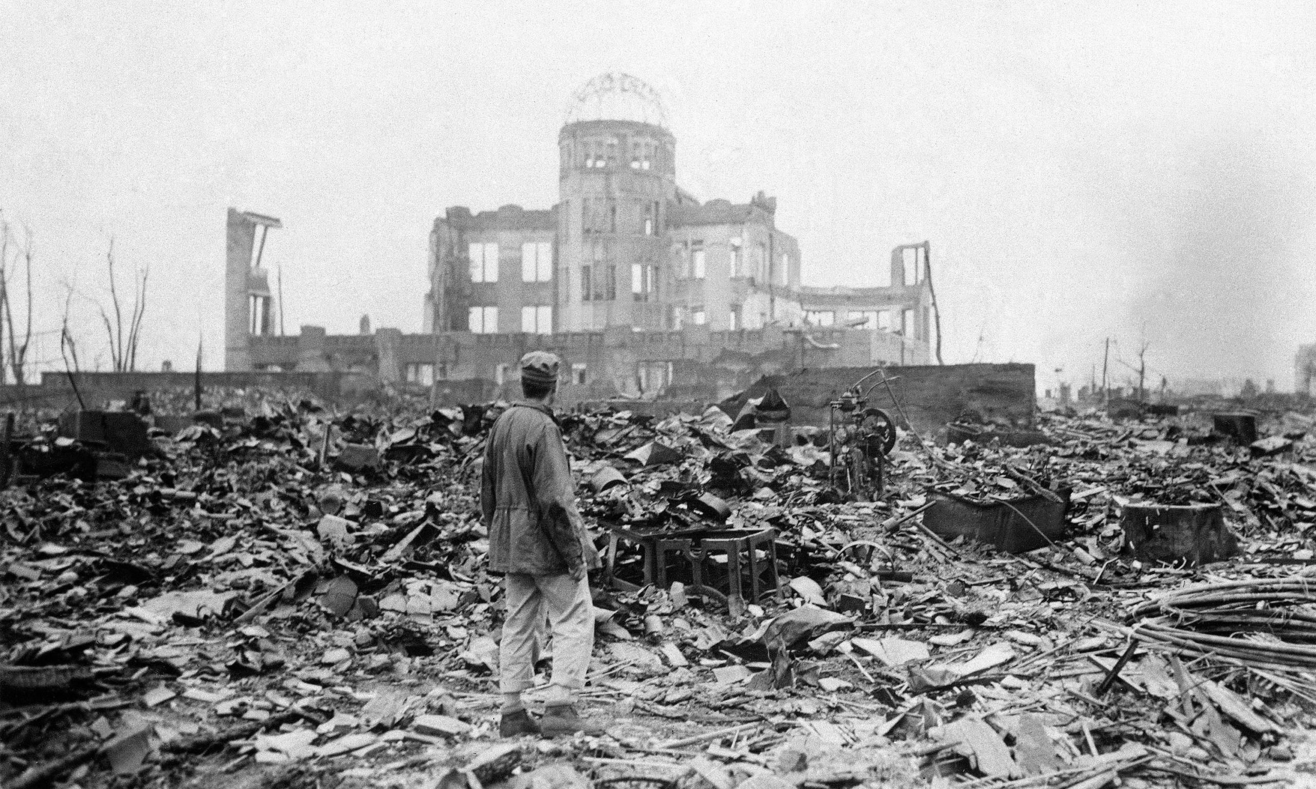 An allied correspondent standing in the rubble in front of the shell of a building that once was a movie theatre in Hiroshima, Japan, a month after the first atomic bomb ever used in warfare was dropped by the US on Monday, August 6, 1945.