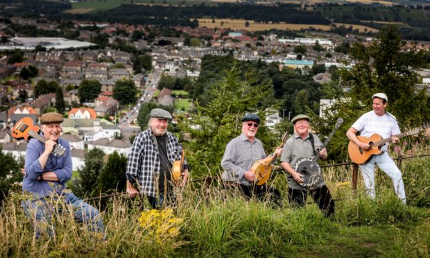 Ian Kennedy and his bandmates at the top of the Law looking over the schemes of Dundee.