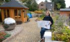 Kirrie Connections activities co-ordinator Gail Robertson at the Kirriemuir Community Garden with some of the newsletters. Pic: Paul Reid