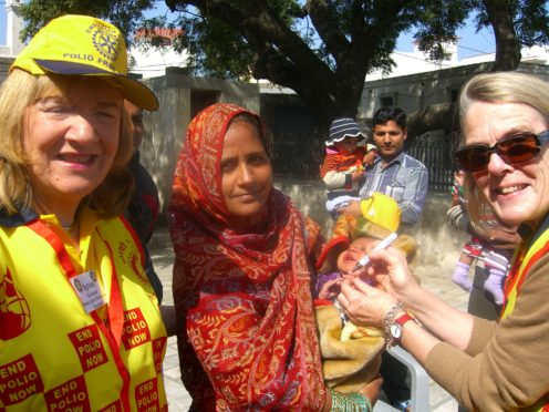 Sylvia Donaldson (left), past president of the Rotary Club of St Andrews, with Irene Constable administering anti-polio vaccine to a child in rural India during a visit to support Rotary's End Polio Now campaign.