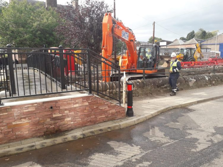 Workers clear debris from Alyth Burn in the town centre.