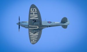 """The """"Thank You NHS"""" Spitfire flies over the Royal Infirmary of Edinburgh."""