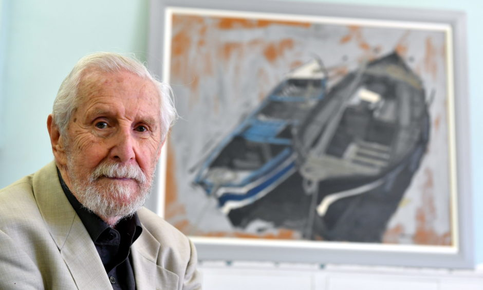Artist James Morrison in 2018 with a fishing boat painting that has hung in Catterline School for decades.