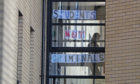 A student walks past a sign at Murano Street Student Village in Glasgow, where Glasgow University students are being tested at a pop up test centre. A range of new measures to combat the rise in coronavirus cases come into force in Scotland on Friday, including a ban on indoor household visits and a curfew for pubs and restaurants. PA Photo. Picture date: Friday September 25, 2020. See PA story SCOTLAND Coronavirus. Photo credit should read: Andrew Milligan/PA Wire